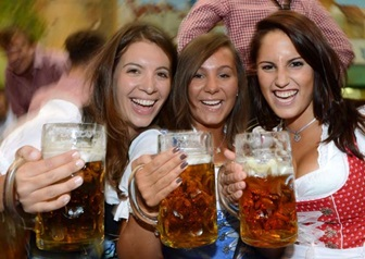 Women wearing traditional Bavarian dresses Dirndl pose with beer mugs under a tent during the Oktoberfest beer festival fair at the Theresienwiese in Munich, southern Germany, on September 27, 2012. The world's biggest beer festival Oktoberfest will run until October 7, 2012. AFP PHOTO / CHRISTOF STACHE
