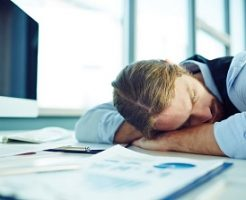 Young tired businessman sleeping by his workplace