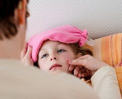 Sick little girl having her body temperature measured